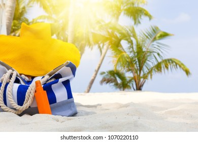 Summer hat and blue stripe bag with sunscreen lotion on sandy tropical beach with coconut palm trees background