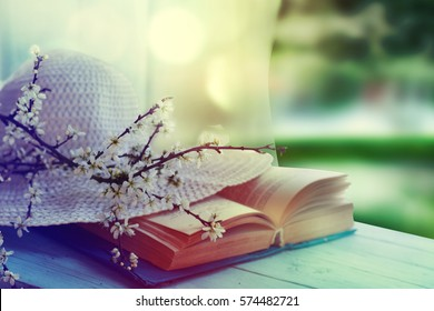 Summer hat,  book and spring blossom on wooden table on garden background.