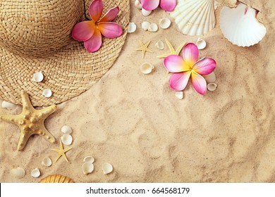 summer hat and seashells on the sand beach. summer frame background