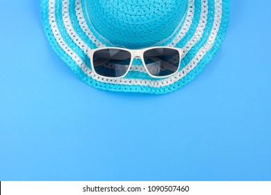 Summer hat with sunglasses. Top view, minimal concept over a blue background. Top border orientation.
