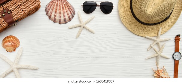Summer hat and sunglasses with wrist watches and shells on white wooden background