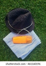 Summer hat, towel and sunscreen on green grass