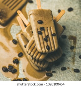 Summer healthy vegan frozen dessert. Flatlay of melting coffee latte popsicles with coffee beans over grey marble background, square crop