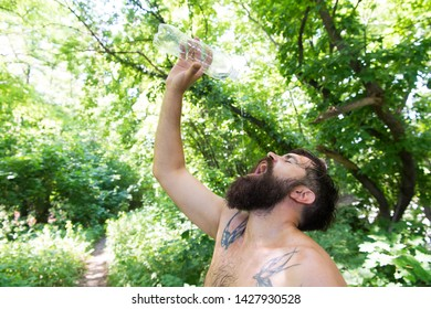 Summer heat. Man thirsty sweaty hipster naked in forest. Heat concept. Bearded tattooed guy relax in nature hot summer day. Hipster wet skin and hair survive heat. Vacation resort. Extreme heat.