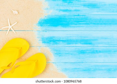 Summer holiday background with colorful flip flops on light blue vintage wood panel, top view with copy space