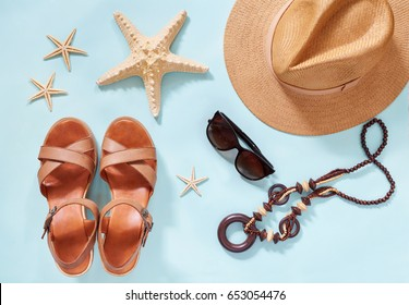 Summer holiday background, flat lay beach women's accessories: straw hat, bracelets, leather sandals, sun glasses, beads and sea stars on blue table. Vacation and travel items. Top view.
