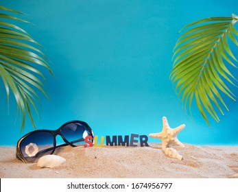 Summer holiday background with palm leaves, seashells, starfish and sunglasses on beach with blue copy space.