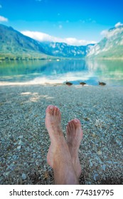 Summer holiday by the lake, barefoot adult caucasian male relaxing on beach pebbles and looking into water and mountains in the distance. Enjoying vacation and nature beauty.
