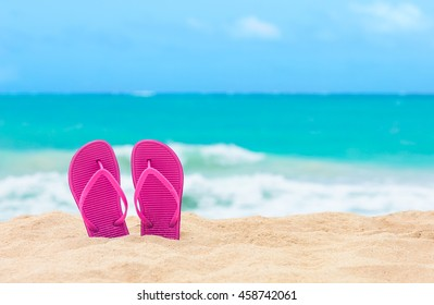 Summer holiday concept. Pair of sandals on the beach.