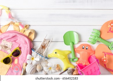 Summer holiday concept, prepare accessories and travel items for kid on white wooden board, flat lay, top view background