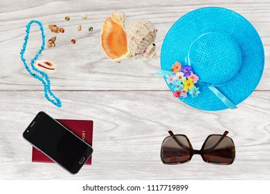 Summer holiday concept, straw hat, passport, smartphone. turquoise chip beads, accessories and travel items over wooden background, flat lay, top view