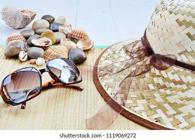 Summer holiday concept, vacation, straw hat, seashells and sunglasses on light blue wooden background