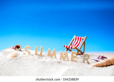 Summer holiday decoration with wooden text, beach chair and sea shall on white sand beach with tropical blue sea and clear blue sky,Image For Love summer holiday vacation travel Concept.