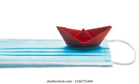 Summer holiday during pandemic crisis. Mask with red paper ship on white background.