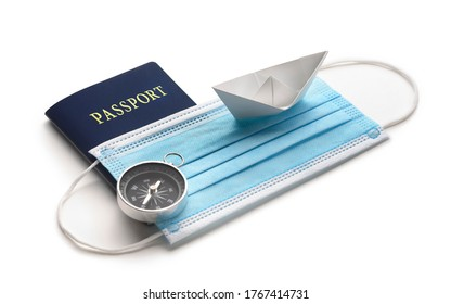 Summer holiday during pandemic crisis. Mask with white paper ship and passport on white background.