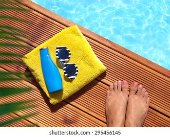 Summer holiday fashion concept -  woman  on a wooden pier at the pool