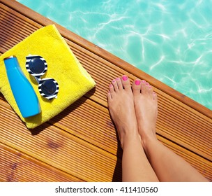 Summer holiday fashion selfie concept - woman on a wooden pier at the pool with summer accessories; sunglasses, towel and sunscreen