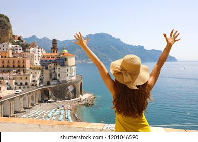 Summer holiday in Italy. Back view of young woman with straw hat and yellow dress with raised arms looking at Atrani village, Amalfi Coast, Italy