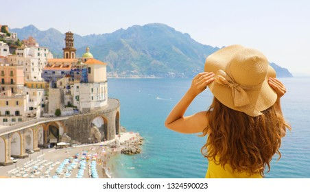 Summer holiday in Italy. Back view of young woman holding her hat with Atrani village on the background, Amalfi Coast, Italy
