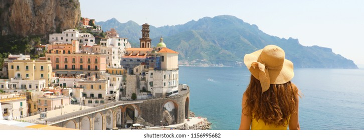 Summer holiday in Italy panorama banner. Back view of young woman with straw hat and yellow dress with Atrani village on the background, Amalfi Coast, Italy.