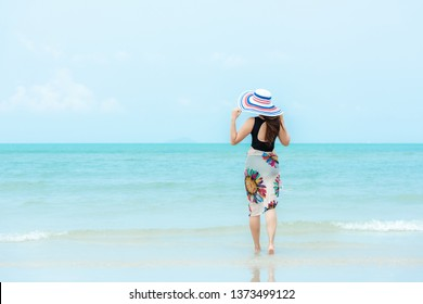 Summer Holiday. Lifestyle woman chill holding big white hat and wearing bikini fashion summer trips walking on the sandy ocean beach. Happy woman enjoy and relax vacation. Lifestyle  Travel Concept