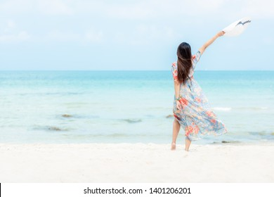 Summer Holiday.  Lifestyle woman wearing fashion summer trips standing on the sandy ocean beach. Happy woman enjoy and relax vacation. Lifestyle and Travel Concept