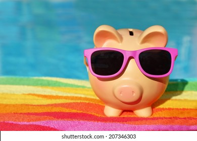 Summer holiday piggy bank with sunglasses in front of a swimming pool
