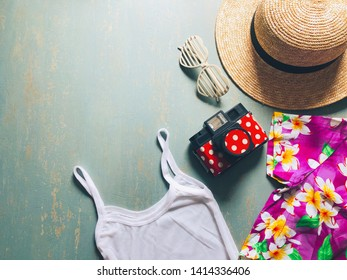 Summer holiday preparation checklist - Straw boater hat with black ribbon, plastic heart shaped glasses, toy camera, white camisole, colorful hawaiian shirt on vintage green background space for text.