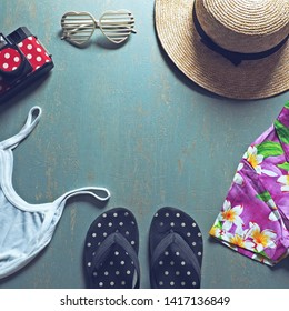 Summer holiday preparation checklist - Straw boater hat with black ribbon, plastic heart shaped glasses, toy camera, flip flop sandal, white camisole, colorful Hawaiian shirt on blue background.