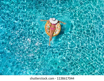Summer holiday relaxation concept: attractive woman with white hat relaxes on a donut shaped float over blue, sparkling pool water