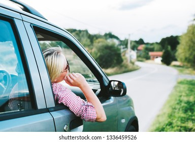 Summer holiday roadtrip travel to countryside. Young hipster blond woman driving car on rural road and having fun summer vacation. Happy girl with sunglasses arriving to mountain village.