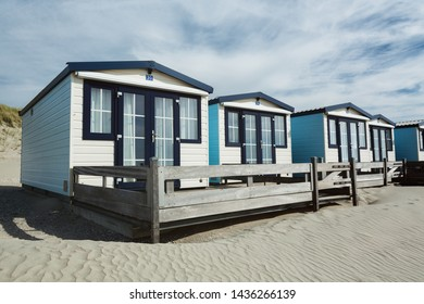 Summer holiday - row of beach houses or bungalows on a sandy beach with dunes behind them.