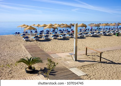 Summer holiday scenery, sandy beach by the blue sea, deckchairs, wooden boardwalk and a shower in Marbella resort on Costa del Sol in Spain