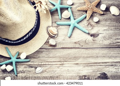 Summer holiday setting with straw hat and seashells on wooden background