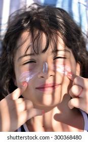 summer holiday, sun protection - girl sunbathing on the beach
