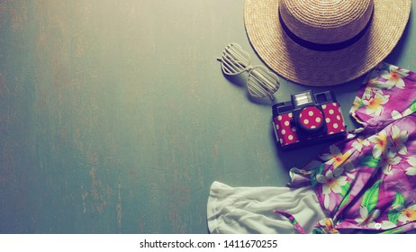 Summer holiday theme preparation checklist - Straw boater hat with black ribbon, plastic heart shaped glasses, toy camera, white camisole, colorful Hawaiian shirt on green background. (vintage filter)