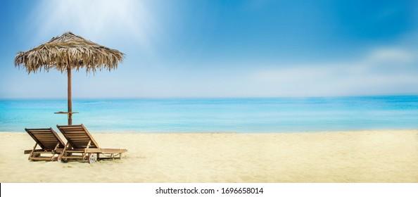 Arrière-plan voyage de vacances d'été. Vacances hôtelières de luxe sur l'île tropicale. Parapluie et chaises longues sur la plage de sable.
