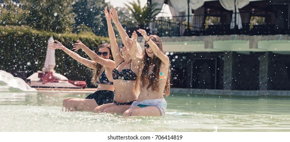 Summer holiday travel girls having fun splashing water and playing in the pool feeling happy in amazing resort, sunglasses, chilling at the hotel pool. Best summer vacation ever in the tropical island