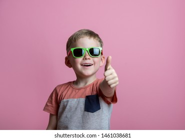 Summer holiday and vacation concept. Happy stylish school boy in sunglasses with thumb up against pink background. Back to school