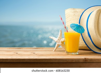 Summer holiday vacation concept with orange juice, hat and bag over sea beach background