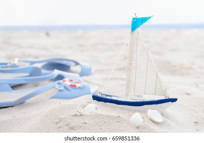 Summer holiday or summer vacation concept with sailing yacht and navy sandals on the beach.