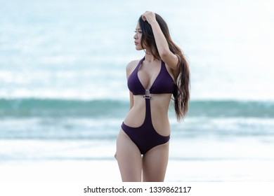 Summer holiday vacation concept. Traveler woman lifestyle in bikini standing and enjoying relaxing on destinations sea beach