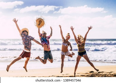Summer holiday vacation travel concept with young group of people friends jumping for happiness and joy at the beach with blue sea and sky in background enjoying nature and  outdoor free leisure