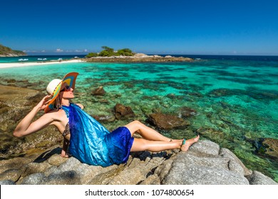 Summer holidays in Andaman sea. Attractive woman with blue sarong sitting on the rocks looking at tropical turquoise sea. Racha Noi island, Rawai, Thailand.Lifestyle female enjoying at Paradise beach.