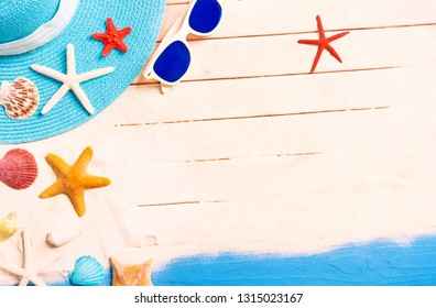 Summer holidays background with starfish and beach accessories -  Conceptual frame of summertime vacation with blue hat , sunglasses and shells on tropical white sand - Top view image with copy space