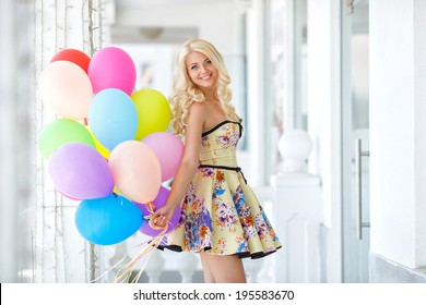 summer holidays, celebration and lifestyle concept - beautiful blonde woman with colorful balloons in the city. Bright summer portrait