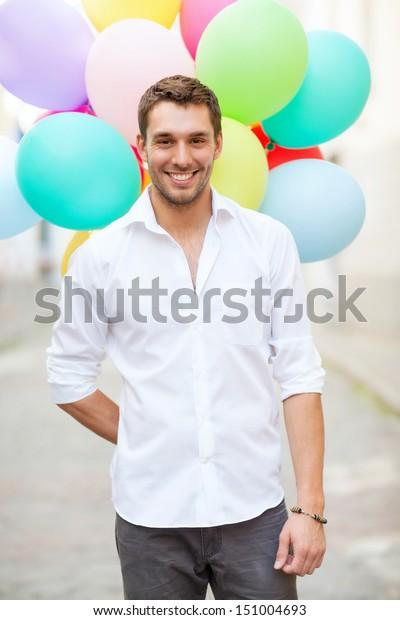Sommerferien, Feiern und Lifestyle-Konzept - Mann mit bunten Ballons in der Stadt