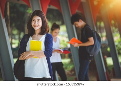 Summer holidays, education, campus and teenage concept - smiling teenage boy in with classmates on the back