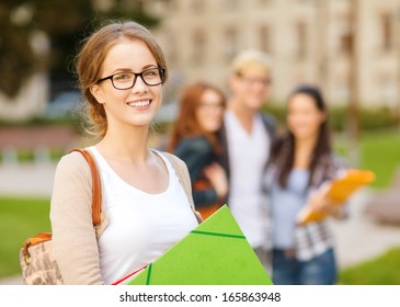 summer holidays, education, campus and teenage concept - smiling female student in black eyeglasses with folders and group in the back