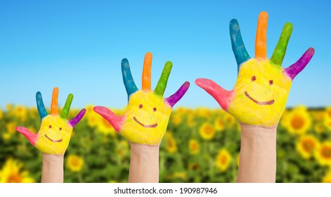 Summer holidays and family concept. Three colorful painted hands with smiling face of family, mother, father and baby on background of sunflowers field in sunny summer's day.